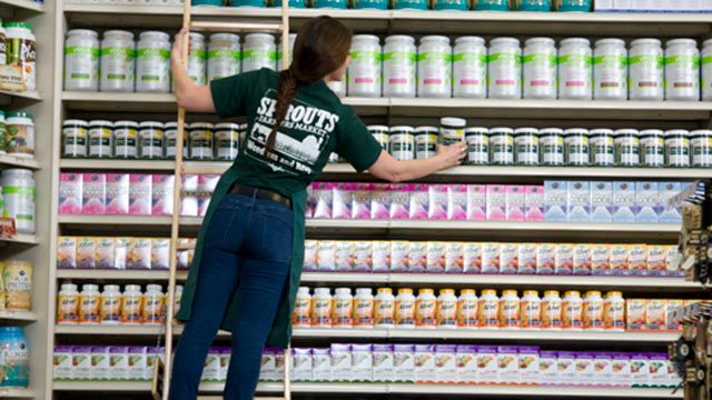 A Sprouts employee on a ladder stocks a shelf.