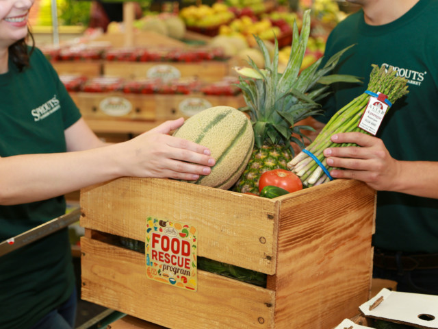 Sprouts employees pack food into a wooden crate
