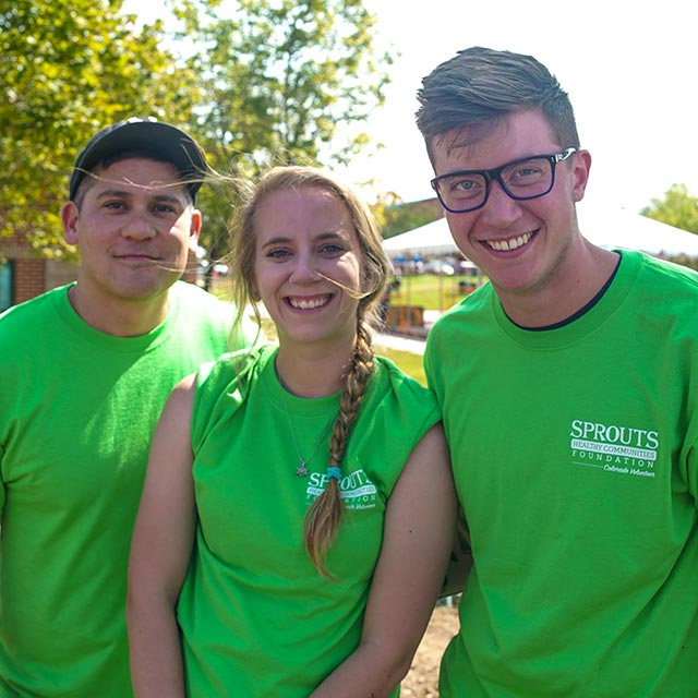 Three Sprouts volunteers in Sprouts Foundation tshirts