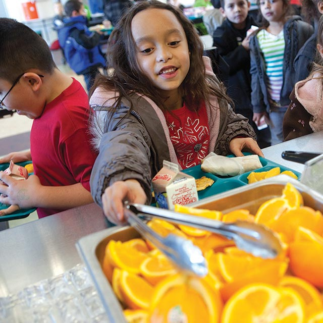A kid selects an orange wedge with tongs