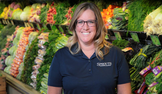 Sprouts manager in front of produce wet rack