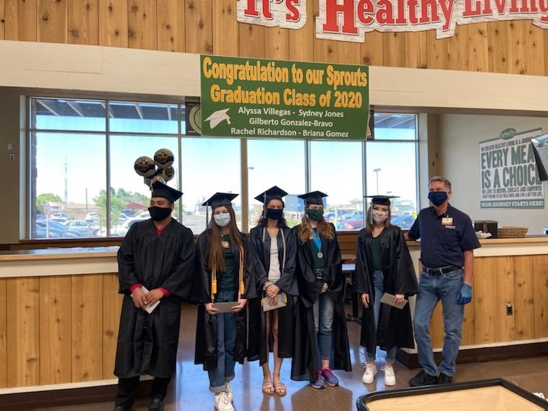 five team members at the front of a Sprouts store in caps and gowns aside the store manager and a sign congratulating them