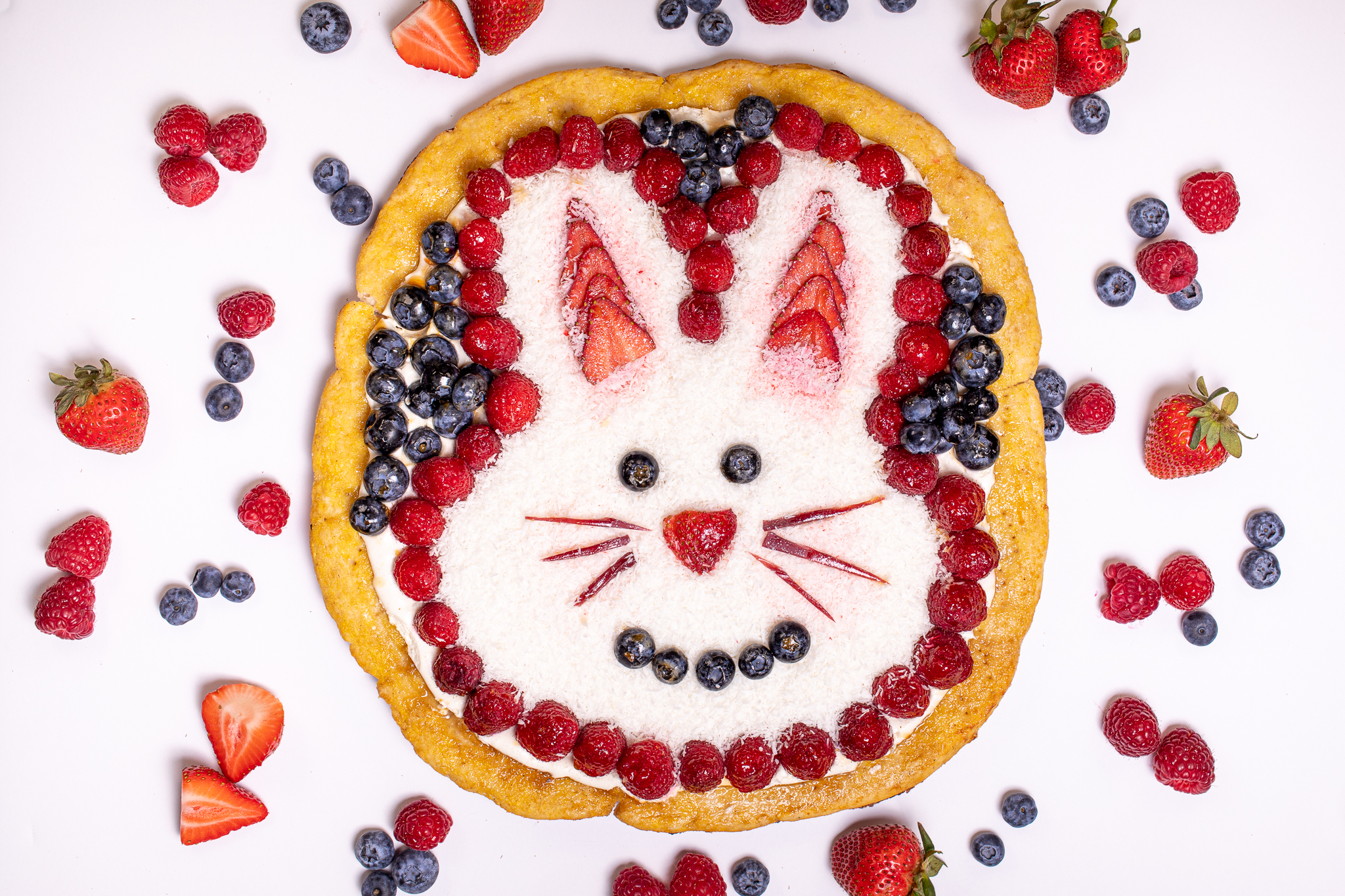 Photo of pizza decorated with fruit and an easter bunny design